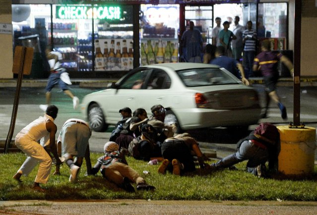 Protesters run to take cover after shots were fired in a police-officer involved shooting in Ferguson, Missouri August 9, 2015. (Photo by Rick Wilking/Reuters)