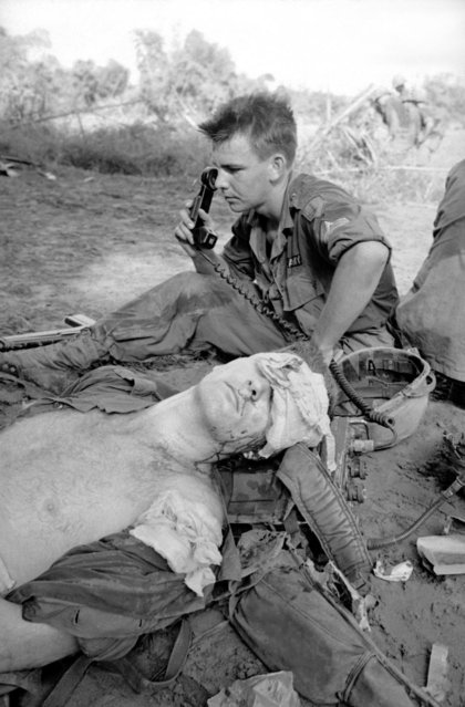 Seriously injured by shrapnel grenades planted in a booby trapped Viet Cong propaganda stall, a U.S. soldier awaits evacuation from Vietnamese jungle by ambulance helicopter being summoned by a radio operator behind him on Dec. 5, 1965
