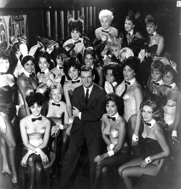 Millionaire publisher of Playboy magazine Hugh Hefner poses with a bevy of bunny girls at one of America's chain of Playboy clubs, 1962. (Photo by Helmut Kretz/Getty Images)