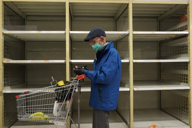 A man wearing face mask stands near an empty shelf of rice at a supermarket in Hong Kong, Thursday, February 6, 2020. Ten more people were sickened with a new virus aboard one of two quarantined cruise ships with some 5,400 passengers and crew aboard, health officials in Japan said Thursday, as China reported 73 more deaths and announced that the first group of patients were expected to start taking a new antiviral drug. (Photo by Vincent Yu/AP Photo)