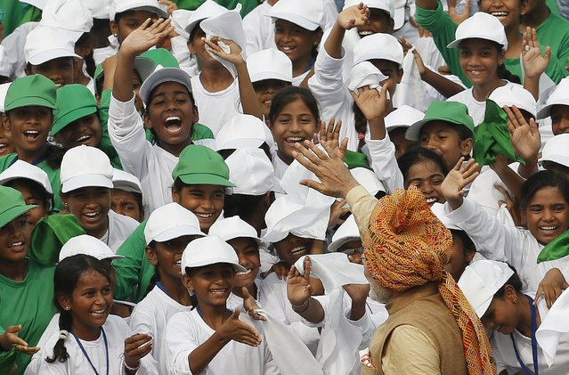 Indian Prime Minister Narendra Modi (wearing turban) waves to school children after addressing the nation from the historic Red Fort during Independence Day celebrations in Delhi, India, August 15, 2015. (Photo by Adnan Abidi/Reuters)