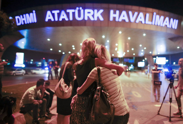 Passengers embrace each other at the entrance to Istanbul's Ataturk airport, early Wednesday, June 29, 2016 following their evacuation after a blast. Suspected Islamic State group extremists have hit the international terminal of Istanbul's Ataturk airport, killing dozens of people and wounding many others, Turkish officials said Tuesday. (Photo by Emrah Gurel/AP Photo)