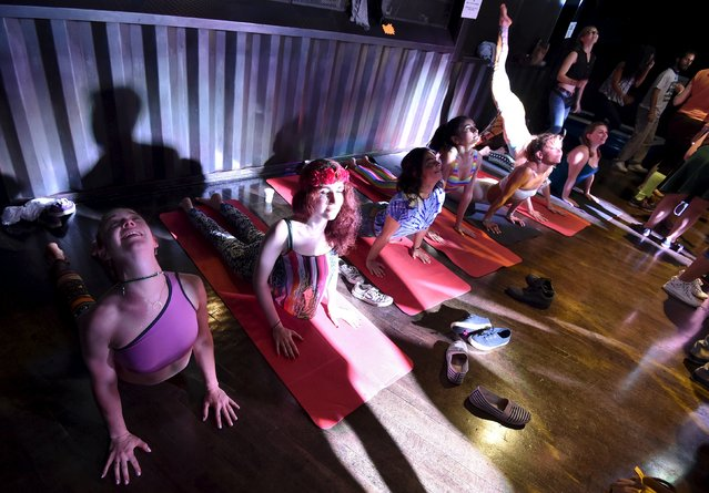 """Club-goers perform yoga stretches at """"Morning Gloryville"""" at the Ministry of Sound in south London August 11, 2015. (Photo by Toby Melville/Reuters)"""