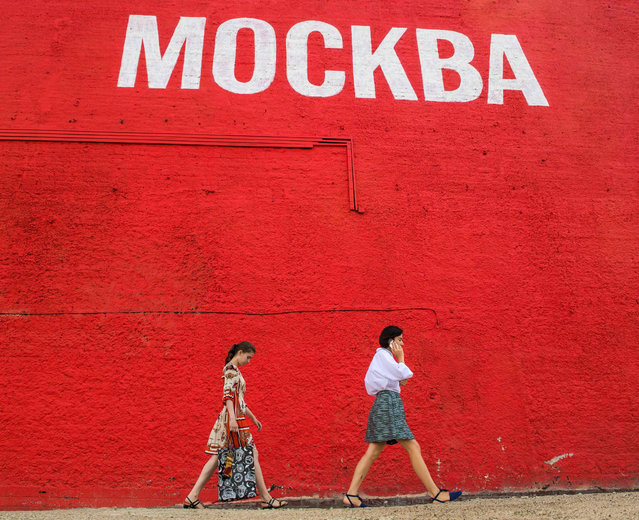 "Pedestrians walk past the word ""Moscow"" in cyrillic alphabet as a wall is painted with an advert for a non- alcoholic beer ahead of the FIFA World Cup August 10, 2017 in downtown Moscow, Russia. (Photo by Mladen Antonov/AFP Photo)"