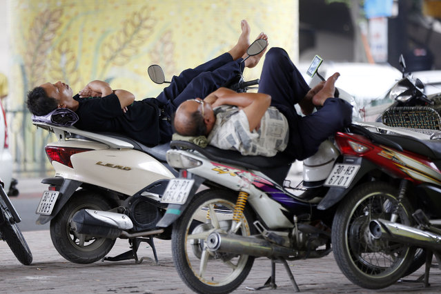 Two motorbike drivers take a nap at a street in Hanoi, Vietnam 30 July 2014. Vietnam's inflation rate increased 1.62 percent in the first seven months of 2014, according to data from the General Statistics Office (GSO). This is considered as the lowest rate in the last 13 years in Vietnam. (Photo by Luong Thai Linh/EPA)