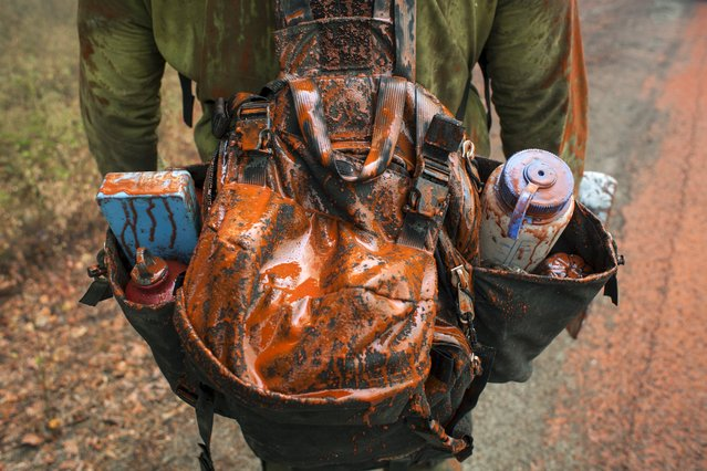 A firefighter's backpack is seen covered in fire retardant dropped from an airplane while battling the Twisp River fire near Twisp, Washington August 20, 2015. (Photo by David Ryder/Reuters)