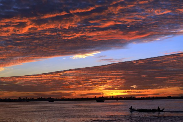 A boat commutes across the Mekong river in Phnom Penh on August 8, 2014. The Mekong is the world's twelth longest river running from the Tibetan Plateau through China's Yunnan province, Myanmar, Laos, Thailand, Cambodia and Vietnam. (Photo by Tang Chhin Sothy/AFP Photo)