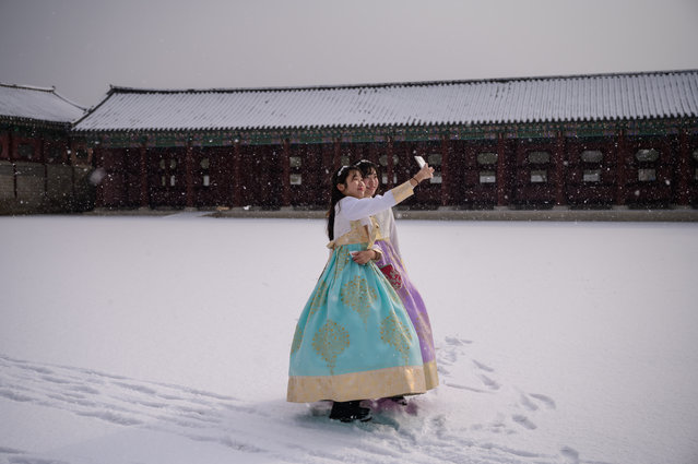 Visitors wearing traditional hanbok dress pose for selfie photos in the snow at Gyeongbokgung palace in Seoul on February 17, 2020. (Photo by Ed Jones/AFP Photo)