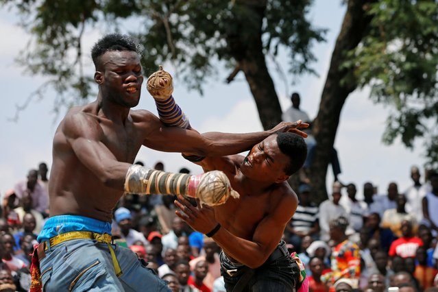 A Dambe boxer punches his opponent during the ancient brutal martial art of Dambe boxing, a sport associated with Hausa people of West Africa during a weekend match in Dei-Dei, Abuja, Nigeria on June 30, 2019. A Nigerian production company is seeking to turn Dambe, a traditional martial art associated with the Hausa people of West Africa, into a sport with a global audience. (Photo by Afolabi Sotunde/Reuters)
