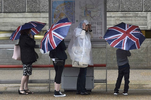 People shelter from the rain at a bus stop in central London, Britain August 26, 2015. (Photo by Toby Melville/Reuters)