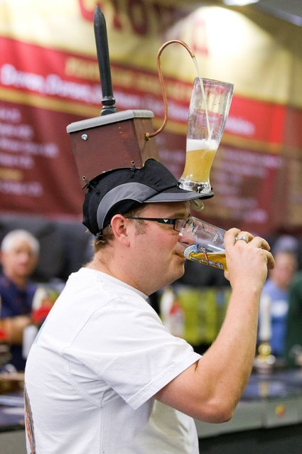 A visitor enjoys a drink at the Great British Beer Festival on silly hat day, at Olympia, London, on August 14, 2014. (Photo by Justin Tallis/PA Wire)