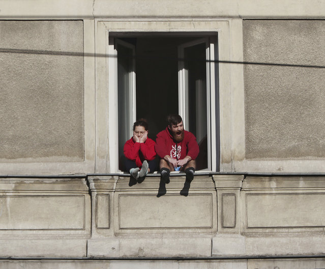 A couple bored with the government-required national isolation at home due to the spreading coronavirus, sits in the 5th floor apartment window on a sunny spring day in downtown Warsaw, Poland, Sunday, March 22, 2020. (Photo by Czarek Sokolowski/AP Photo)