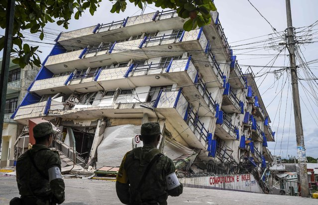 Soldiers stand guard a few metres away from the Sensacion hotel which collapsed with the powerful earthquake that struck Mexico overnight, in Matias Romero, Oaxaca State, on September 8, 2017. Mexico's most powerful earthquake in a century killed at least 35 people, officials said Friday, after it struck the Pacific coast, wrecking homes and sending families fleeing into the streets. (Photo by Victoria Razo/AFP Photo)