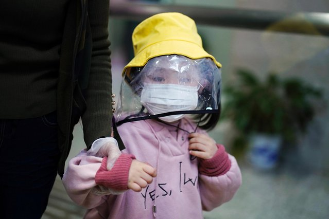 A child wearing a face mask and a face shield is seen at a railway station in Xianning of Hubei province, the epicentre of China's coronavirus disease (COVID-19) outbreak, March 25, 2020. (Photo by Aly Song/Reuters)