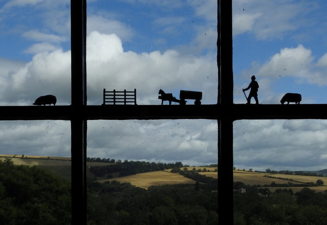 Miniature agricultural figures are seen on a window of a cottage overlooking farmland in Shropshire, central England, Britain July 27, 2017. (Photo by Toby Melville/Reuters)