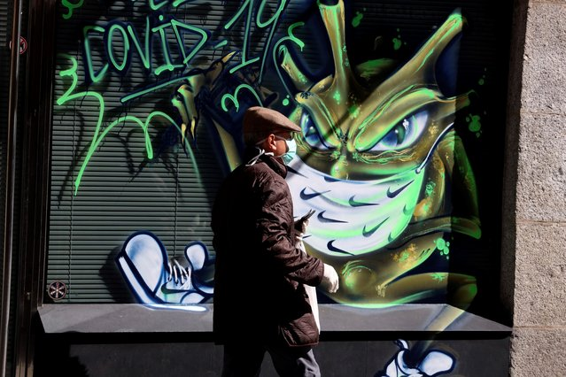 A man wearing a face mask and gloves walks past a graffiti of a cartoon depicting the novel coronavirus currently wreaking havoc on the world in Salamanca, Spain, 24 March 2020. Spanish authorities announced that 514 deaths from the COVID-19 disease caused by the SARS-CoV-2 coronavirus were recorded in only one day on 23 March, elevating the total death toll in the Mediterranean country to 2,696 people, with almost 40,000 confirmed infections. Spain faces the 10th consecutive day of national lockdown. (Photo by Jm Garcia/EPA/EFE)