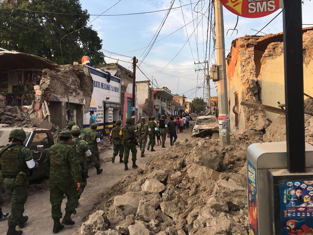 Soldiers walk past piles of rubble from buildings felled by a 7.1 earthquake, in Jojutla, Morelos state, Mexico, Tuesday, September 19, 2017. The earthquake stunned central Mexico, killing at least 139 people as buildings collapsed in plumes of dust. (Photo by Carlos Rodriguez/AP Photo)