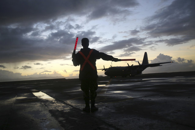 A military C-130 lands to evacuate survivors of Typhoon Haiyan at dusk, Friday, November 15, 2013 in Tacloban city, Leyte province, central Philippines. Typhoon Haiyan, one of the most powerful storms on record, hit the country's eastern seaboard November 8, leaving a wide swath of destruction. (Photo by Wong Maye-E/AP Photo)
