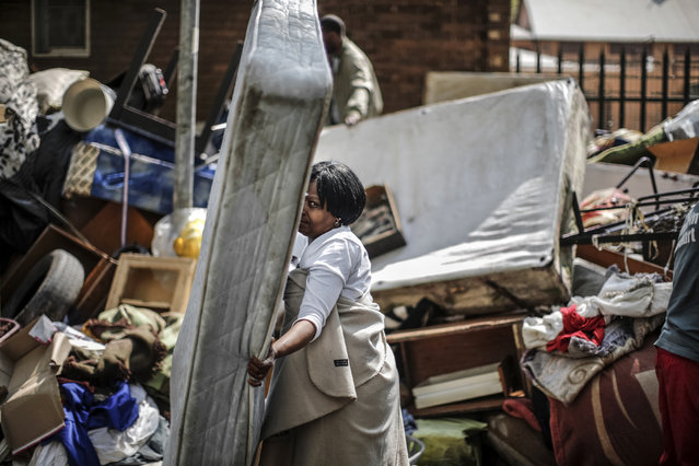 A woman salvages a mattress from a pile of furnitures left in a street of the popular down town district of Hillbrow on September 1, 2015 following the execution of an eviction order on an occupied building. (Photo by Marco Longari/AFP Photo)