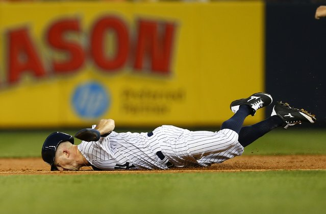 Brett Gardner #11of the New York Yankees dives into second base on the back end of an attempted double during the first inning in a MLB baseball game at Yankee Stadium on September 3, 2014 in the Bronx borough of New York City.  Gardner was tagged out on  the play. (Photo by Rich Schultz/Getty Images)