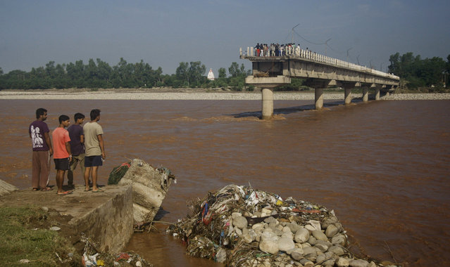 People look at a bridge across the Tawi River that was damaged in the floods at Mandal village on the outskirts of Jammu, India, Sunday, September 7, 2014. The flooding, the worst in 50 years, has killed more than a hundred people across the Himalayan region. (Photo by Channi Anand/AP Photo)