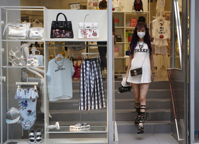 A woman wearing a mask to prevent contracting MERS walks out from a clothing shop at Myeongdong shopping district in central Seoul, South Korea, June 11, 2015. (Photo by Kim Hong-Ji/Reuters)