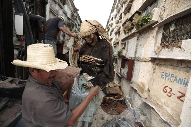 A grave cleaner holds the mummified body of a woman during exhumation works at the Verbena cemetery in Guatemala City April 17, 2013. (Photo by Jorge Dan Lopez/Reuters)