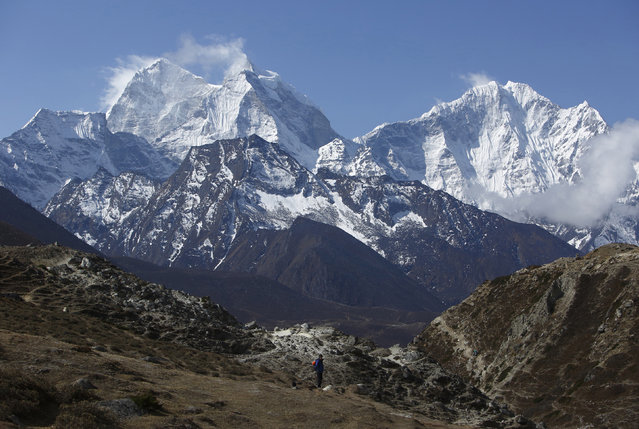 A trekker walks in front of Mount Thamserku while on his way back from Everest base camp near Pheriche in Solukhumbu District May 3, 2014. (Photo by Navesh Chitrakar/Reuters)