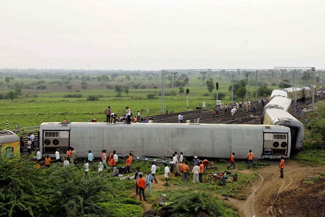 People gather at the site of a train accident at Martur, in Gulbarga district, about 600 kilometers (370 miles) north of India's technology hub of Bangalore, Saturday, September 12, 2015. Two trains derailed in India on Saturday. The other incident happened near the northern hill town of Kalka, in Himachal Pradesh state after three coaches of a special tourist train went off the tracks. (Photo by AP Photo)