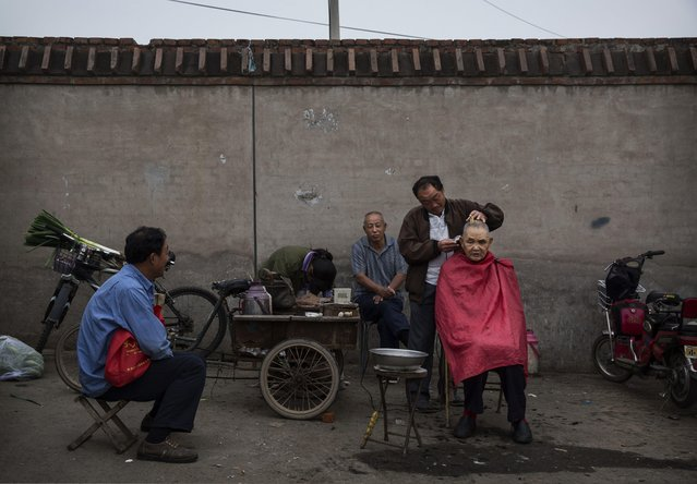 A Chinese barber cuts a laborer's hair at a local market on September 26, 2014 in Beijing, China. (Photo by Kevin Frayer/Getty Images)