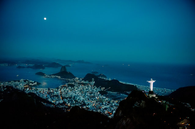 """Corcovado with its iconic Christ the Redeemer statue overlooking Rio de Janiero. """"Visible from nearly every part of the city, and here sharing the skyline with the moon"""". (Photo by David Alan Harvey/Magnum Photos/The Guardian)"""