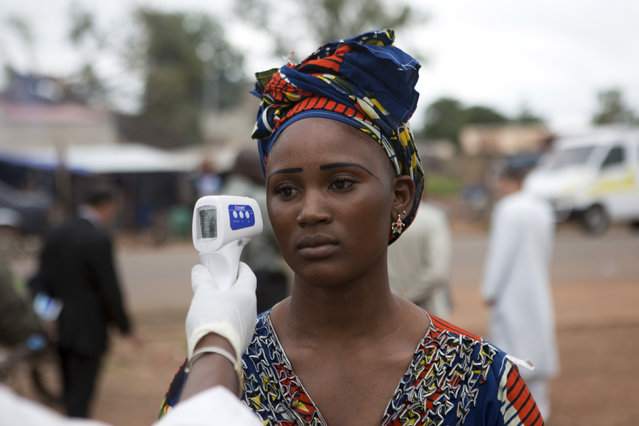 A health worker checks the temperature of a woman entering Mali from Guinea at the border in Kouremale October 2, 2014. The worst Ebola outbreak on record was first confirmed in Guinea in March but it has since spread across most of Liberia and Sierra Leone, killing more than 3,300 people, overwhelming weak health systems and crippling fragile economies. (Photo by Joe Penney/Reuters)