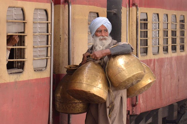 An Indian milkman carries milk containers as he boards a train at a railway station in Amritsar on February 26, 2015. (Photo by Narinder Nanu/AFP Photo)