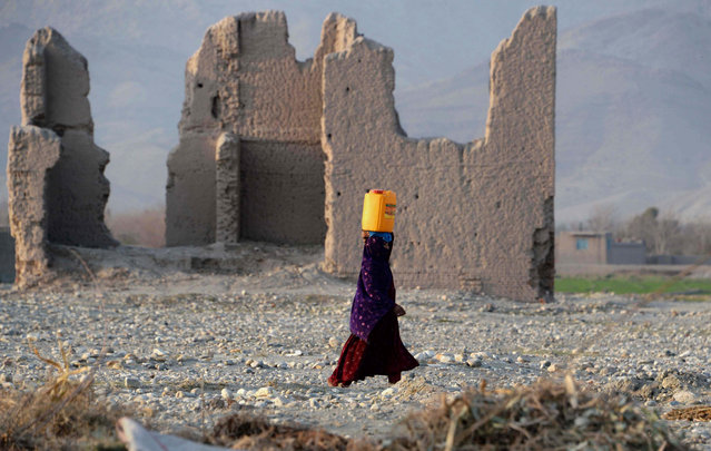 In this photograph taken on February 12, 2015, an Afghan Kuchi resident carries a water canister past ruins of a building destroyed during the Afghan-Soviet war on the outskirts of Jalalabad in Nangarhar province. (Photo by Noorullah Shirzada/AFP Photo)