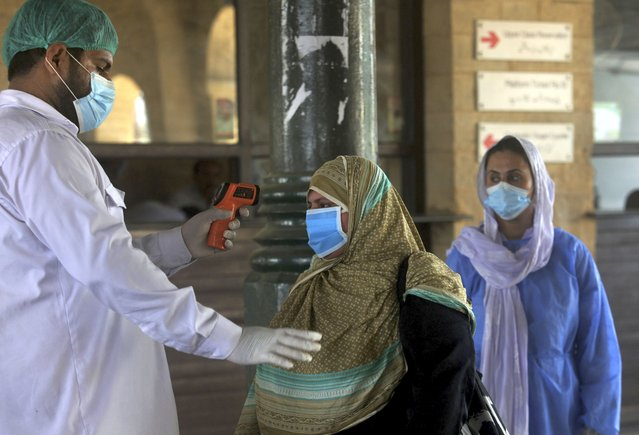 A railway worker checks the body temperature of a woman wearing a protective mask to help curb the spread of the coronavirus, on her arrival at a railway station to board on a train, in Karachi, Pakistan, Saturday, June 6, 2020. (Photo by Fareed Khan/AP Photo)