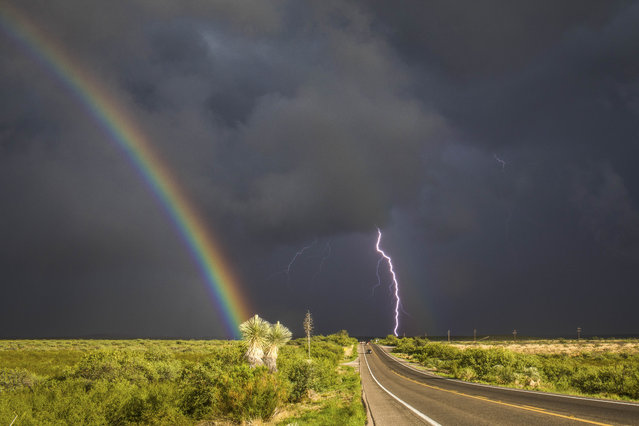 A rainbow and lightening during a storm southeast of St. David, Ariz., on July 28, 2017. (Photo by Mike Olbinski/Caters News Agency)