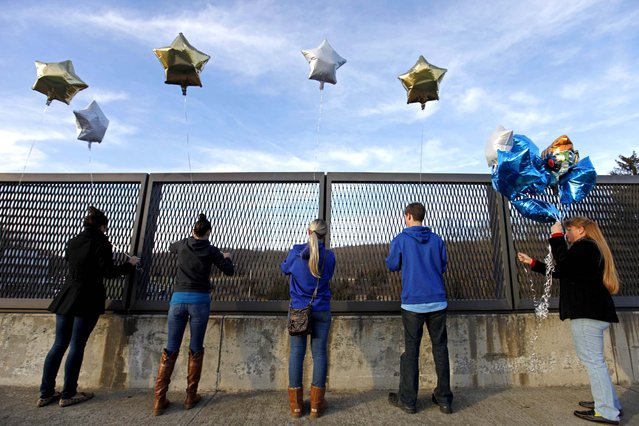 Suada Likovic, Chelsea Crain, Kristin Hoyt, Jeffrey Hoyt and Linda Hoyt, all of Danbury, tie balloons to an overpass up the road from the Sandy Hook Elementary School. (Photo by David Goldman/Associated Press)