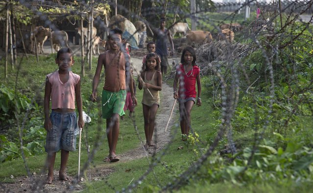 Indian children stand by a fence on the India-Bangladesh border at Jhalchar, in the northeastern Indian state of Assam, Friday, September 2, 2016. Chief Minister of Assam state Sarbananda Sonowal has sought help from the central government in sealing the porous border, one of the core issues of the ruling Bharatiya Janata Party's election campaign in Assam. (Photo by Anupam Nath/AP Photo)