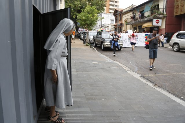 In this September 30, 2017 photo, a nun watches the annual LGBQT march in Asuncion, Paraguay. A lack of legal protections and prevalent macho attitudes have long stoked discrimination against lesbians, gays, bisexuals and transgender people in the poor, mostly Roman Catholic country. (Photo by Jorge Saenz/AP Photo)