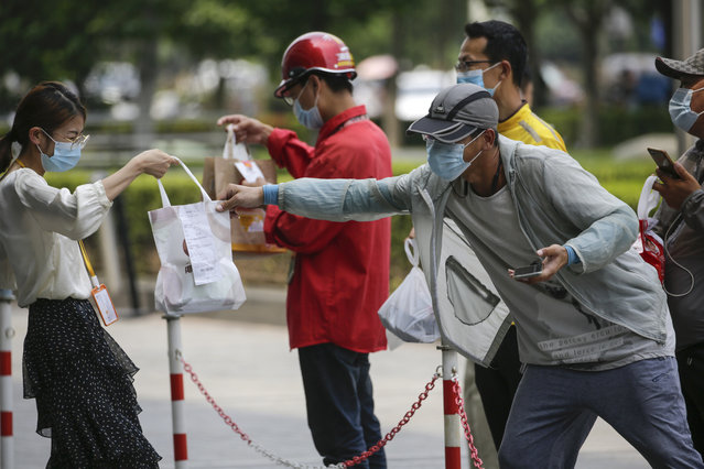 A food delivery man wearing a face mask to protect against the new coronavirus stands behind a barricade line passing a foods to a masked woman outside an office building in Beijing, Wednesday, July 22, 2020. Numbers of cases in China's latest virus outbreak continued to fall Wednesday, with several new cases in the northwestern region of Xinjiang. (Photo by Andy Wong/AP Photo)