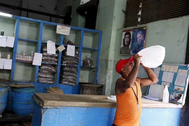 """A man looks into a plastic bag while standing inside a subsidised state store, or """"bodega"""", where Cubans can buy basic products with a ration book they receive annually from the government  in Havana September 18, 2015. (Photo by Carlos Garcia Rawlins/Reuters)"""
