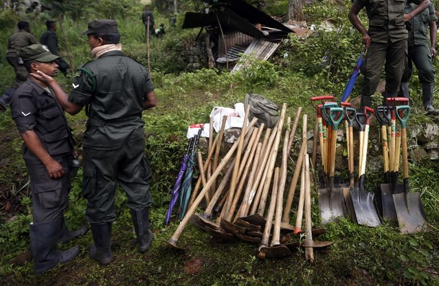 Members of a military rescue team stand near stacks of shovels and hoes at the site of a landslide at the Koslanda tea plantation near Haldummulla October 30, 2014. (Photo by Dinuka Liyanawatte/Reuters)