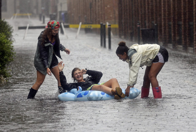 Anna Wilson, center, laughs as she plays with friends Madi Kois, left, and Wesli Jones on a flooded street in Charleston, S.C., Saturday, October 3, 2015. Rain pummeling parts of the East Coast showed little sign of slackening Saturday, with record-setting precipitation prolonging the soppy misery that has been eased only by news that powerful Hurricane Joaquin will not hit the U.S. (Photo by Chuck Burton/AP Photo)