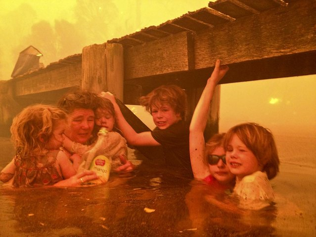 In this January 4, 2013, photo provided by the Holmes family, Tammy Holmes and her grandchildren take refuge under a jetty as a wildfire rages near them  in Dunalley,Australia, on January 9, 2013. The family credits God with their survival from the fire that destroyed around 90 homes there. (Photo by Tim Holmes)