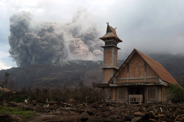 In this photograph taken on October 25, 2014, Mount Sinabung volcano erupts with ash clouds behind an abandoned church, as seen from Karo District on Sumatra island. Super heated lava and giant ash clouds reaching two kilometers into the air spewed from the crater of Mount Sinabung volcano threatening villages during its recent series of eruptions. (Photo by Sutanta Aditya/AFP Photo)