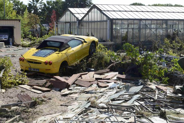Debris surrounds a damaged Ferrari after flooding caused by torrential rain in Biot, France, October 4, 2015. (Photo by Jean-Pierre Amet/Reuters)