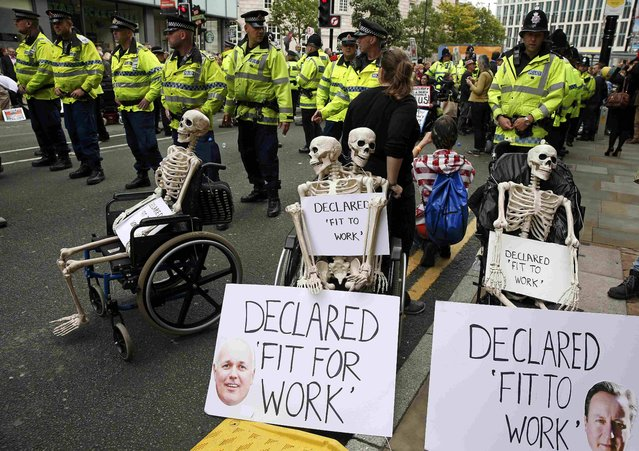 Police officers form a line outside the main entrance diring a demonstration outside the conference hall at the Conservative Party Conference in Manchester,  Britain October 5, 2015. (Photo by Phil Noble/Reuters)
