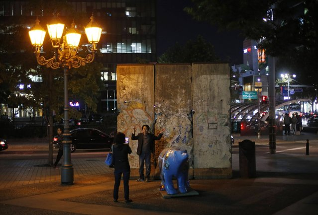 A woman takes a photograph of her husband in front of part of the Berlin Wall at Berlin square in Seoul October 17, 2014. (Photo by Kim Hong-Ji/Reuters)