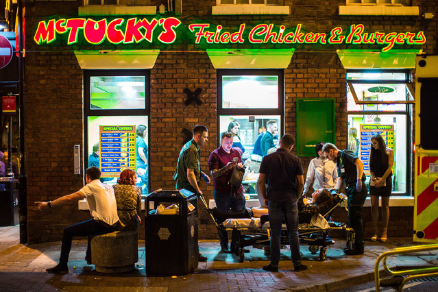 A woman is carried in to an ambulance on a trolley outside McTucky's Fried Chicken and Burgers, in the Gay Village, Manchester, UK on September 11, 2016. (Photo by Joel Goodman/London News Pictures)