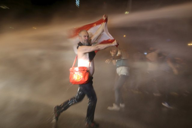 A protester carries a Lebanese flag while sprayed with water from a police water cannon in Martyr square, downtown Beirut, Lebanon October 8, 2015. (Photo by Aziz Taher/Reuters)